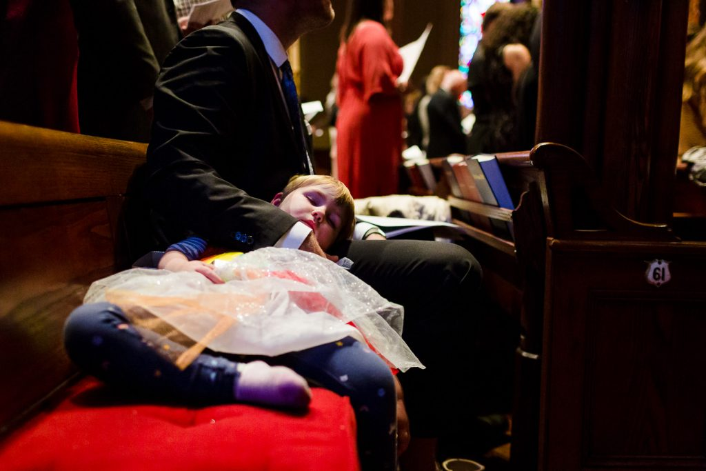 A little girl falls asleep in the pew at a wedding