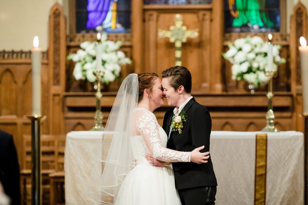 Two brides share a first kiss at their episcopal wedding ceremony