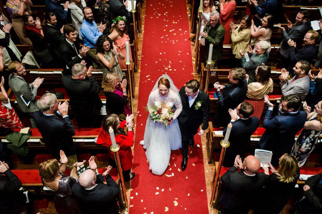 Two brides walk down a red aisle at their church wedding