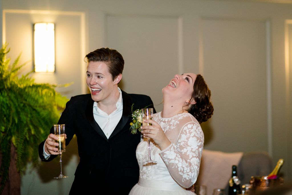 Two brides hold champagne glasses and laugh hysterically at wedding speeches