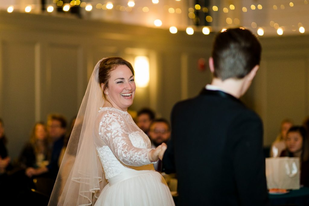 Two brides dance under twinkle lights at their wedding
