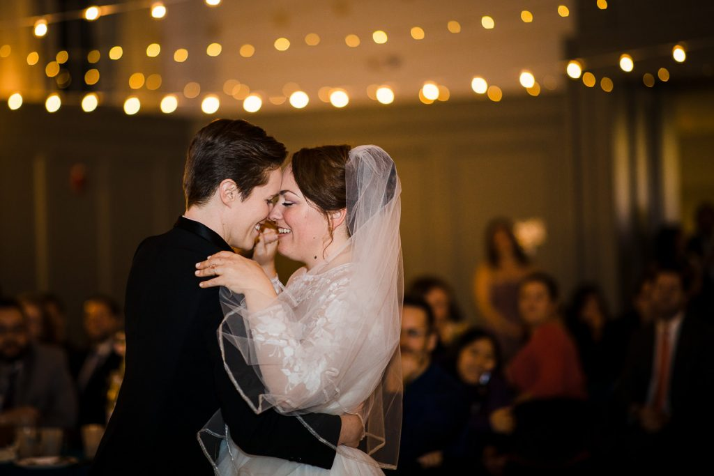 Two brides touch foreheads during the first dance at their westport ct wedding