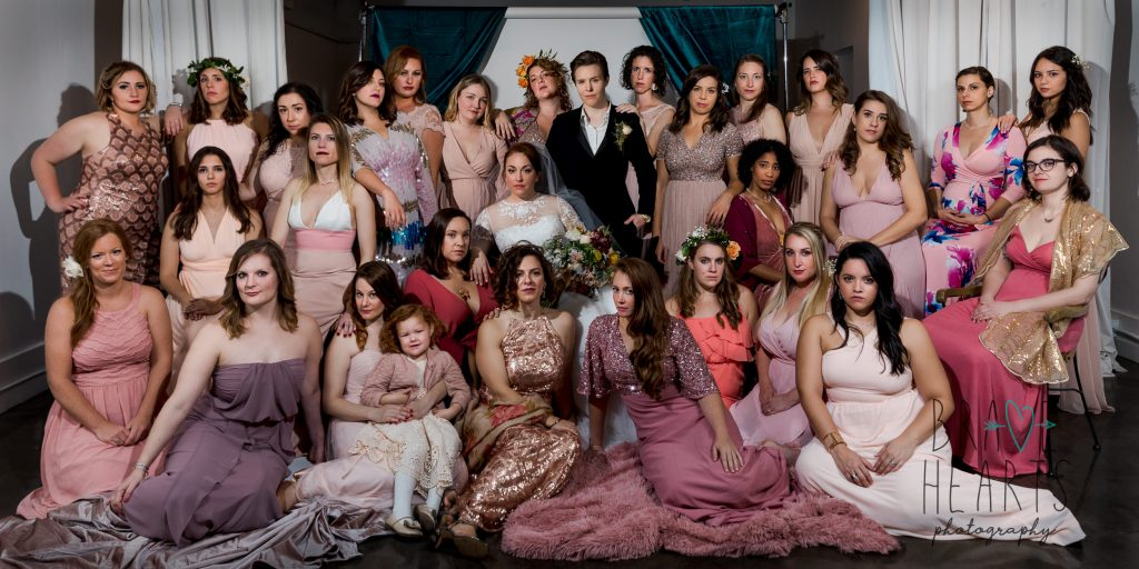 A large group wedding photo of two brides and their bridesmaids styled after vanity fair covers