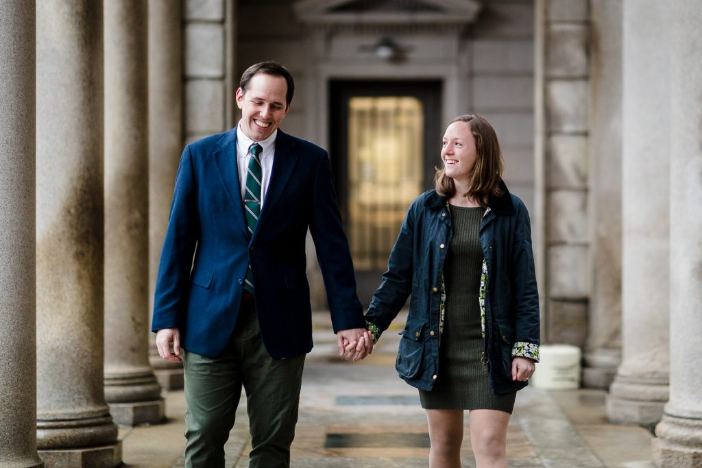 A man and woman walk hand in hand under the portico at the providence superior court during their engagement photo session
