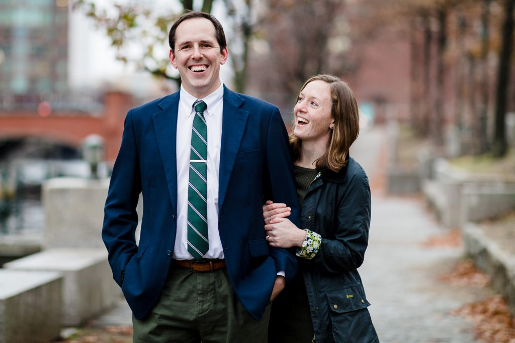A man and woman laugh during their engagement photo session along the waterfront in providence