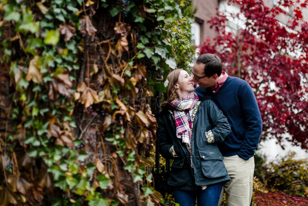 A man and woman kiss next to an ivy covered wall near benefit street in providence ri