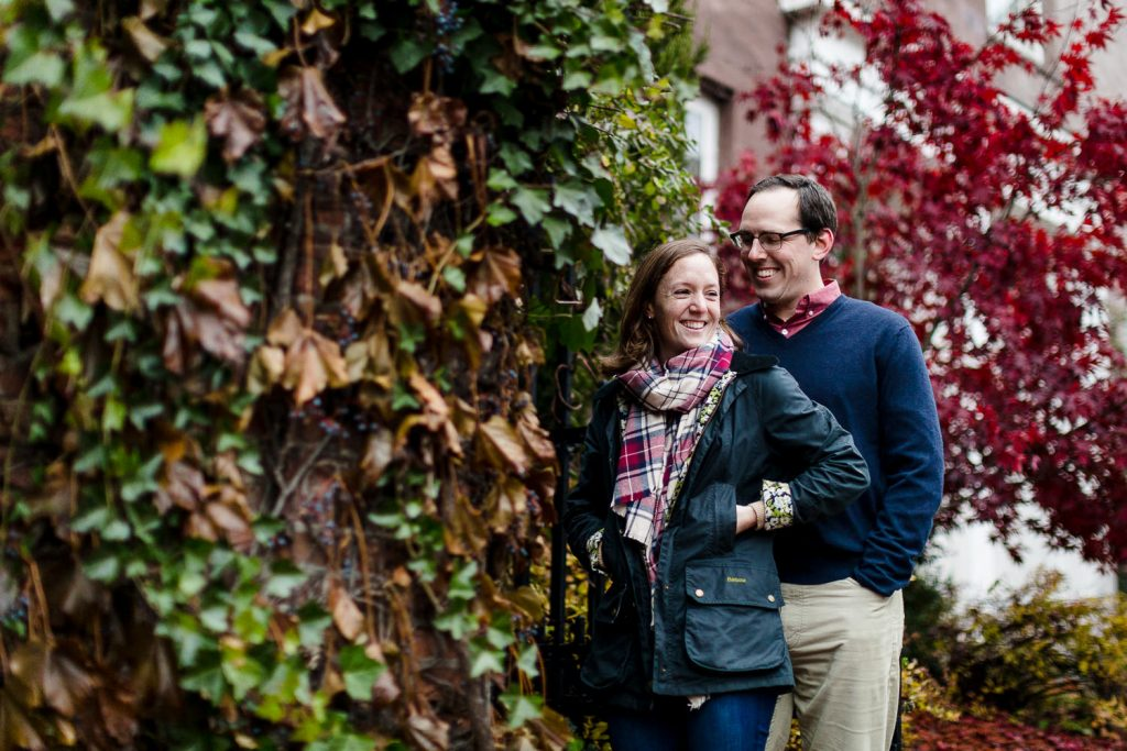 A man and woman snuggle next to an ivy covered wall during their providence ri engagement photos