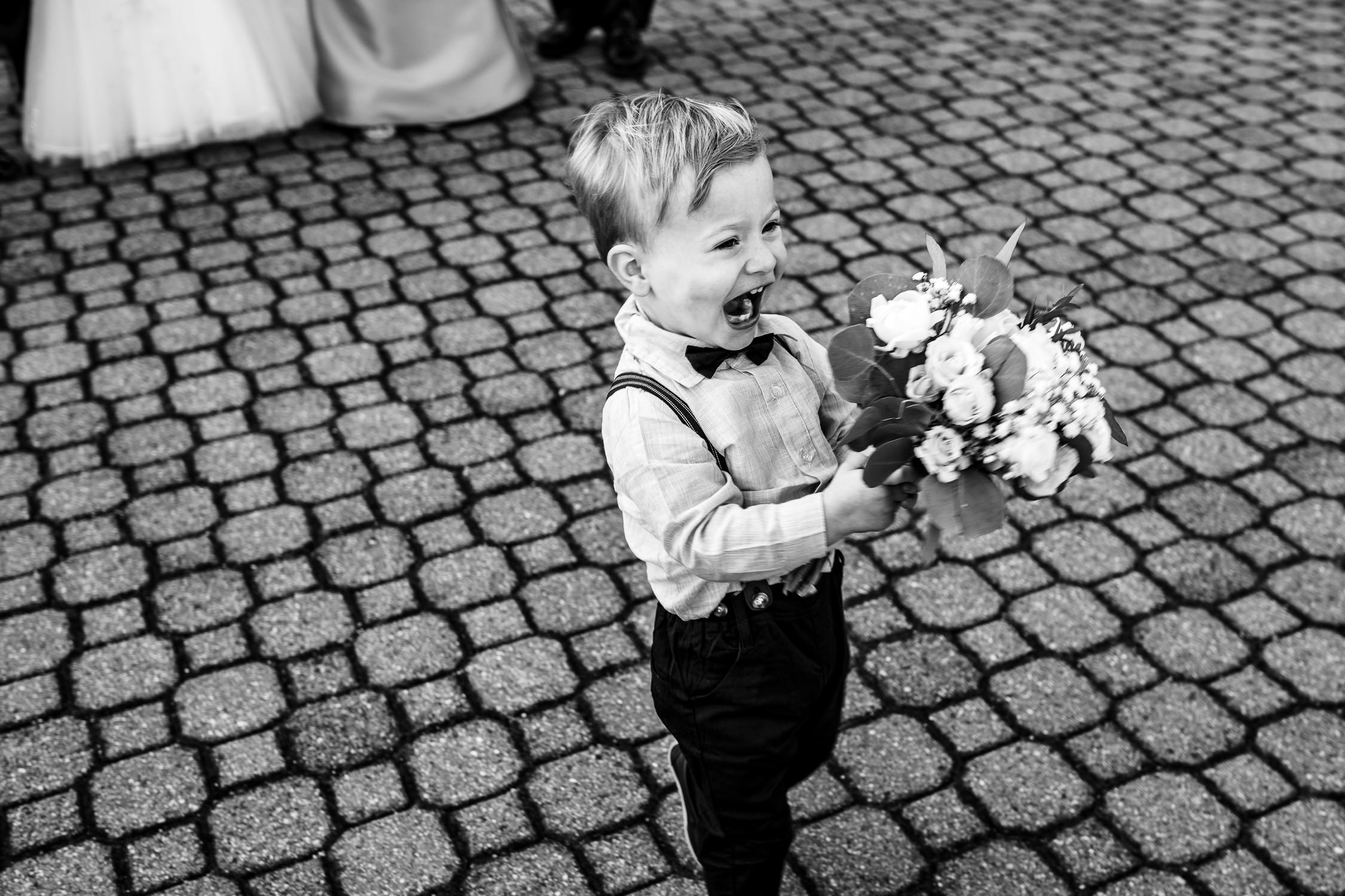 A little boy runs away laughing with a wedding bouquet