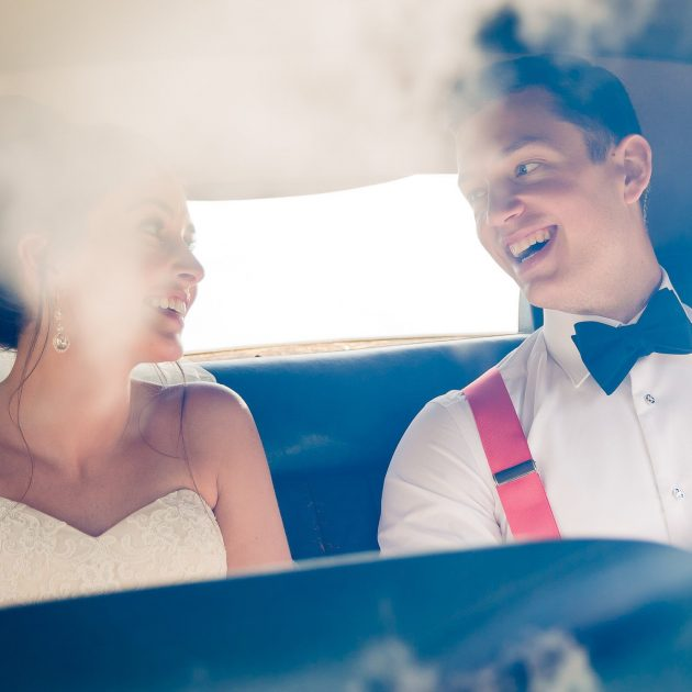 Bride and groom laugh in car outside wedding at Branford House in Groton CT