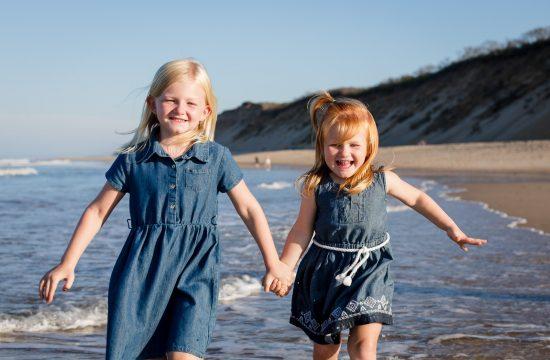 Two girls run down beach hand in hand at cape cod beach family photos