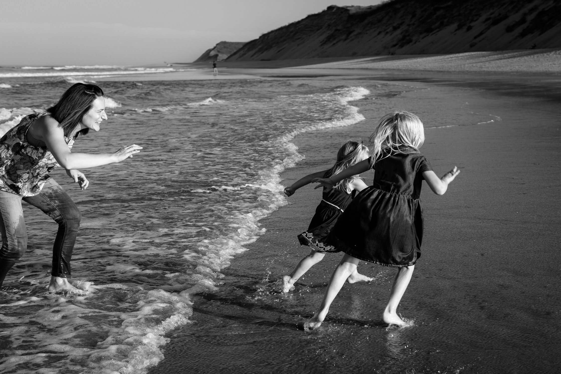 Two girls run away from mom at cape cod family photo session