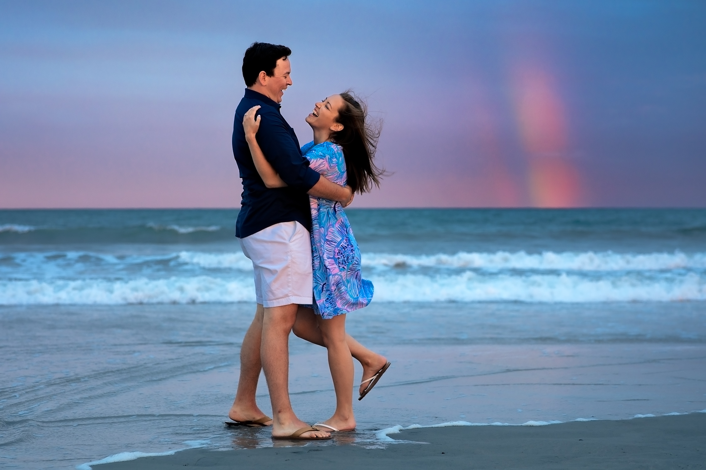 A man and woman hug and laugh on a beach with a rainbow behind them during their eastons beach newport engagement session