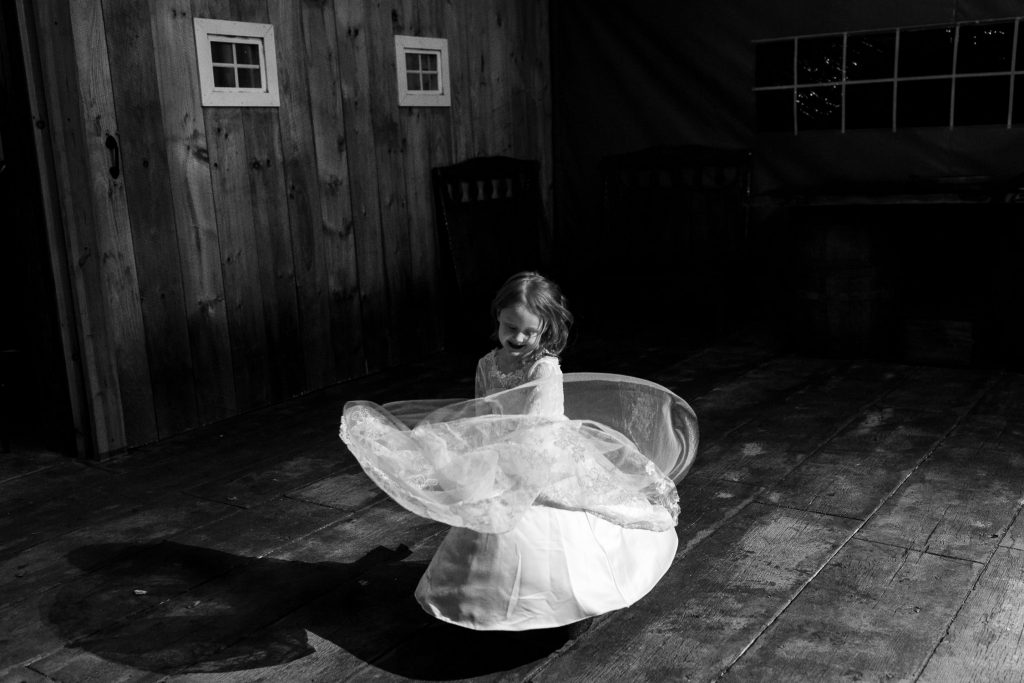 flower girl twirling alone at five bridge barn wedding