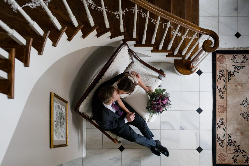 Bride and groom kiss in lobby of Five Bridge Inn wedding