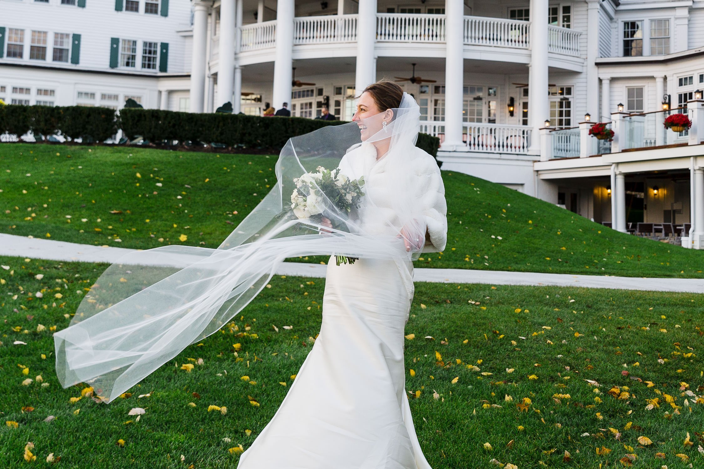Brides laughs as veil blows in wind in front of The Sagamore Resort wedding
