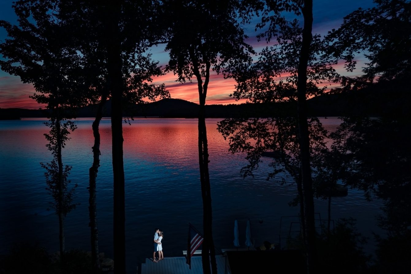 Couple kisses by a lake at sunset in new hampshire