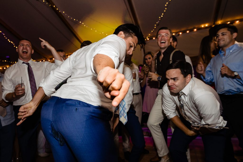 Man points to ripped pants butt at Newport wedding