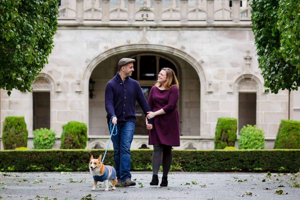 Couple and their corgi walk the front driveway at Ochre Court in Newport RI at their engagement