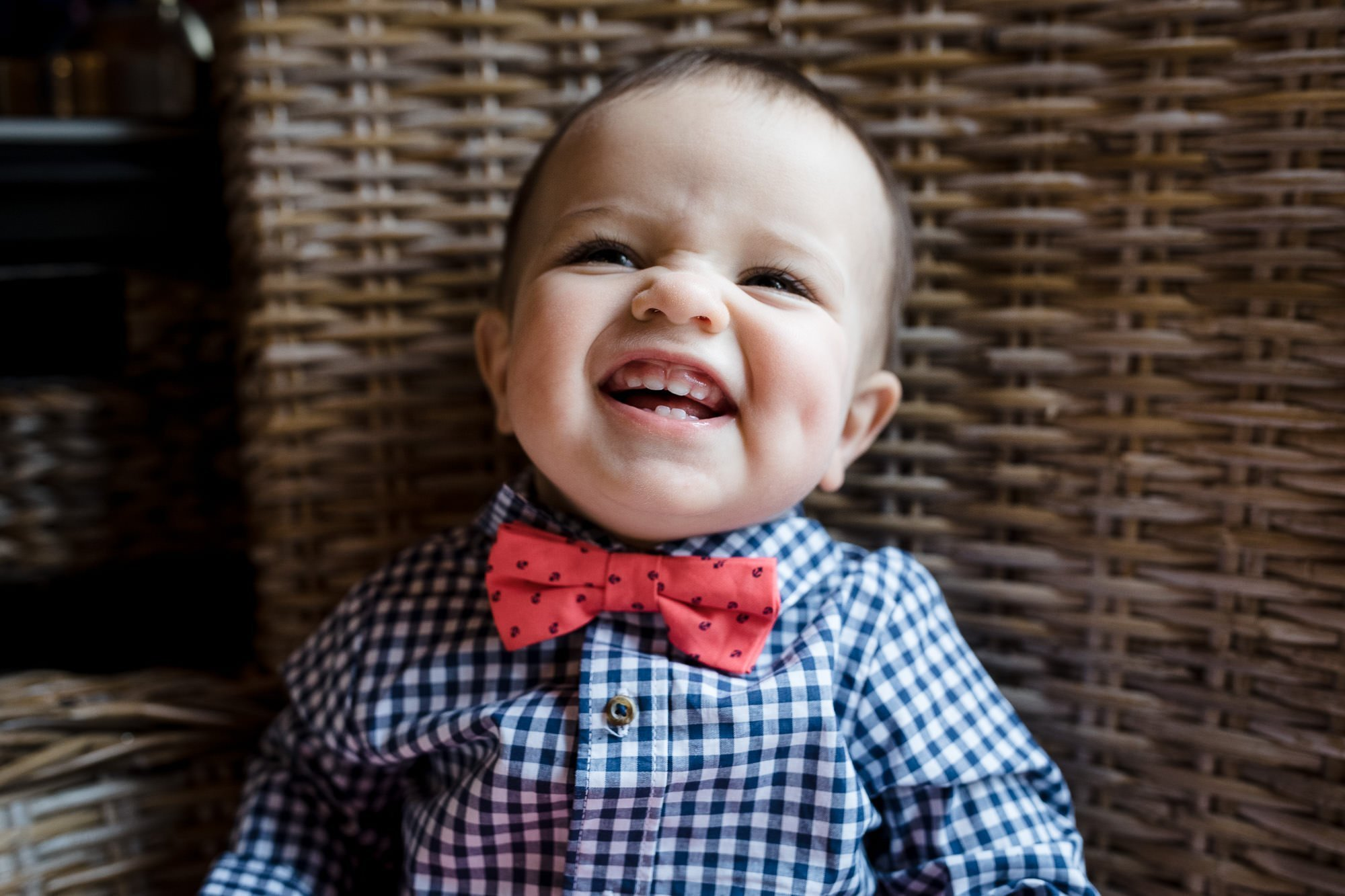 A little boy laughs hysterically in a wicker chair wearing a blue check shirt with pink bowtie during a rhode island documentary family photo session.
