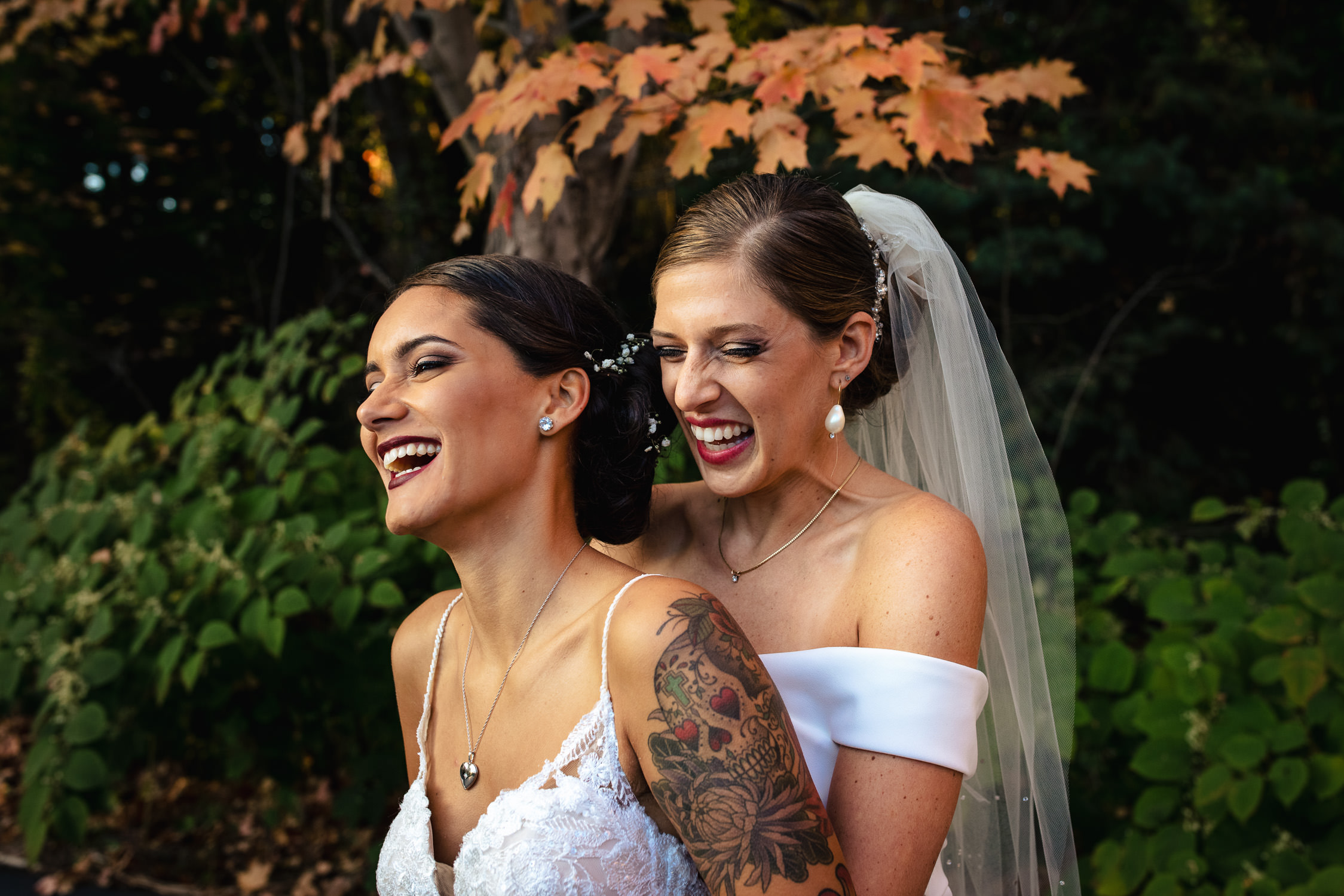 Two brides laughing and spooning