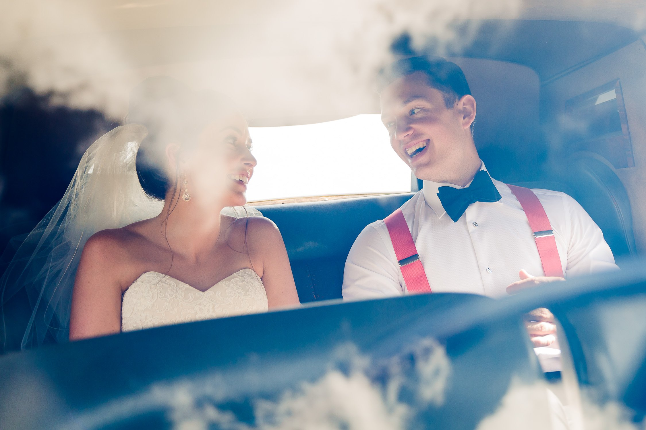 Bride and groom laugh in backseat of car at southern connecticut wedding