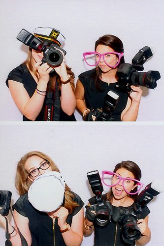 two wedding photographers pose in photo booth with cameras at cape cod wedding