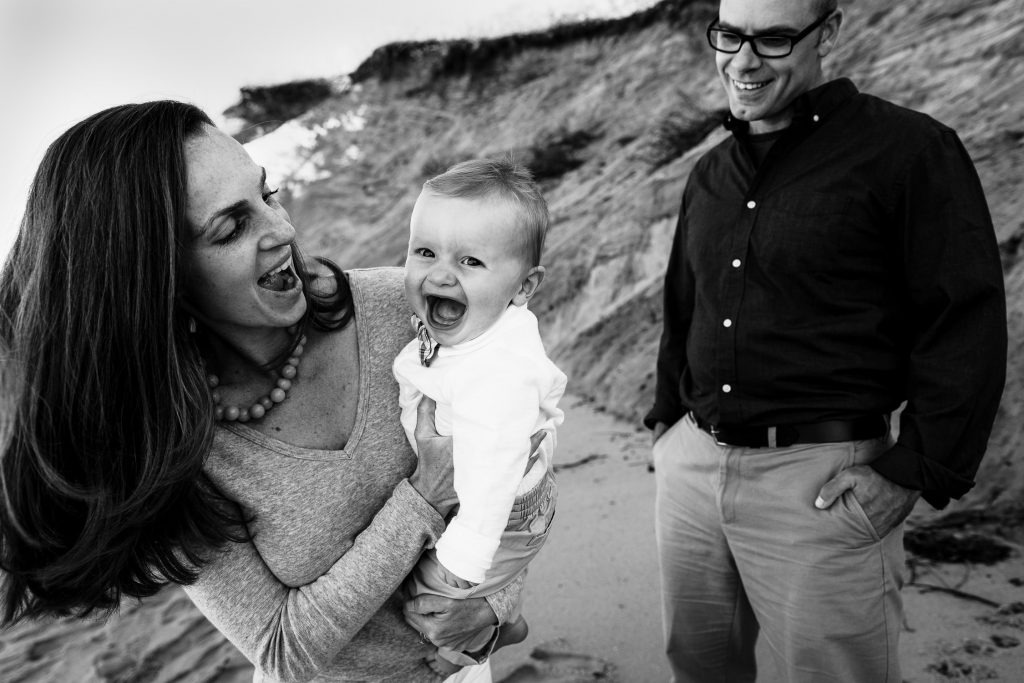 Mom and baby laugh as dad watches at wellfleet cape cod beach