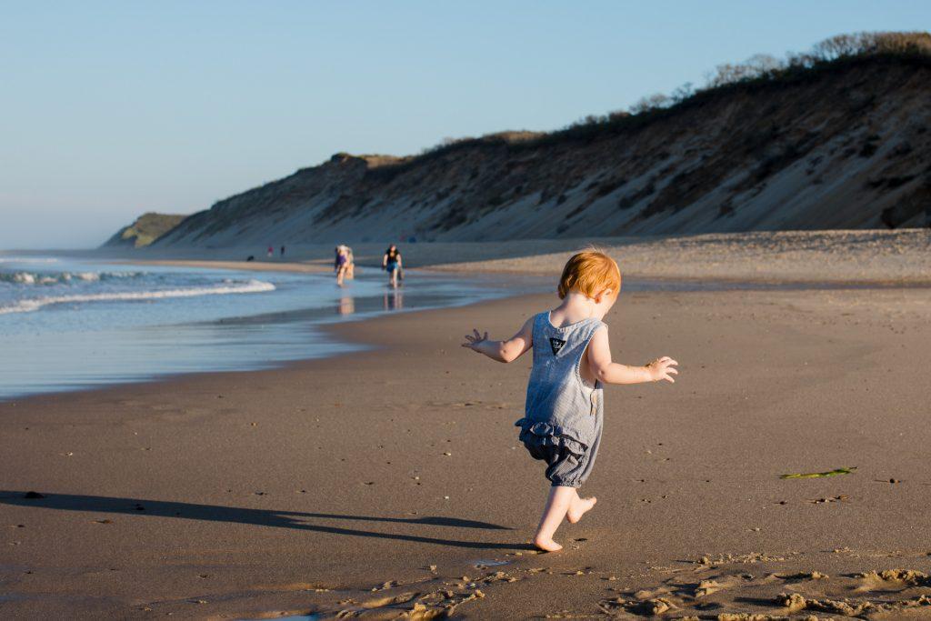 Toddler walks uneasily down beach in wellfleet ma