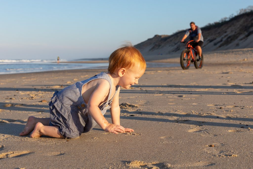 Baby crawls on beach with biker in background at wellfleet family session