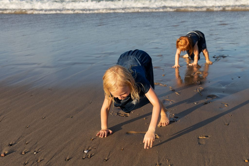 Two girls play on beach at Wellfleet massachusetts family photo session