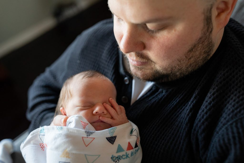 A dad looks down at his newborn baby who has her hand over her eye