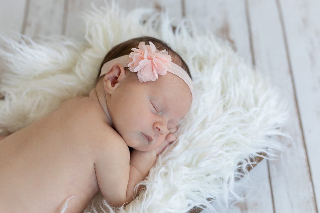 A newborn baby asleep on white fur and white barnwood floors