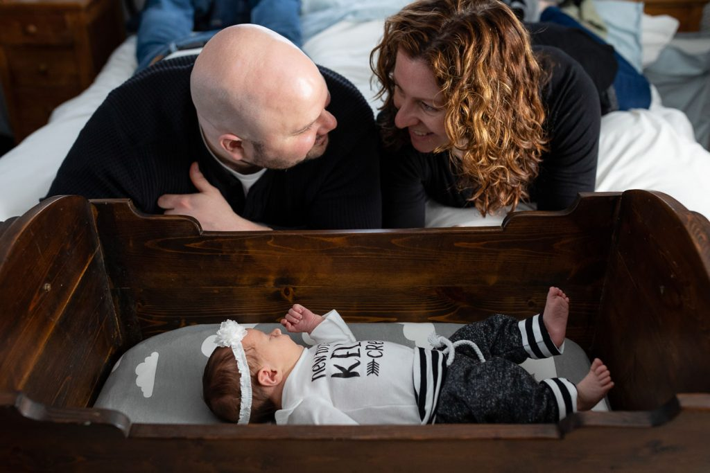 A mom and date look at each over their newborn baby in a cradle