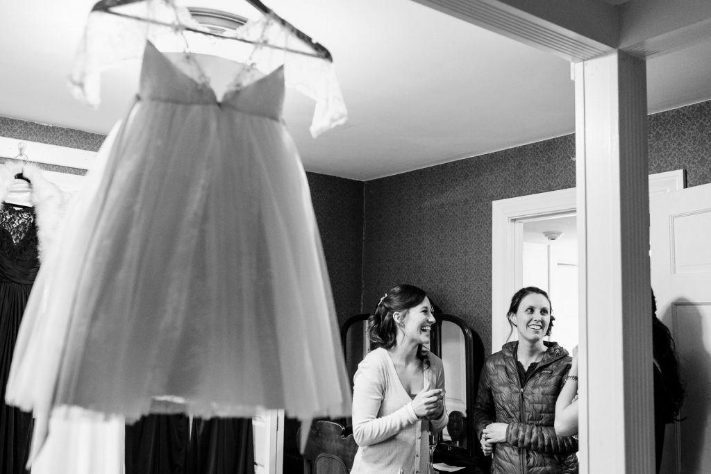The bride laughing with her friends as her daughters flower girls dress hangs overhead