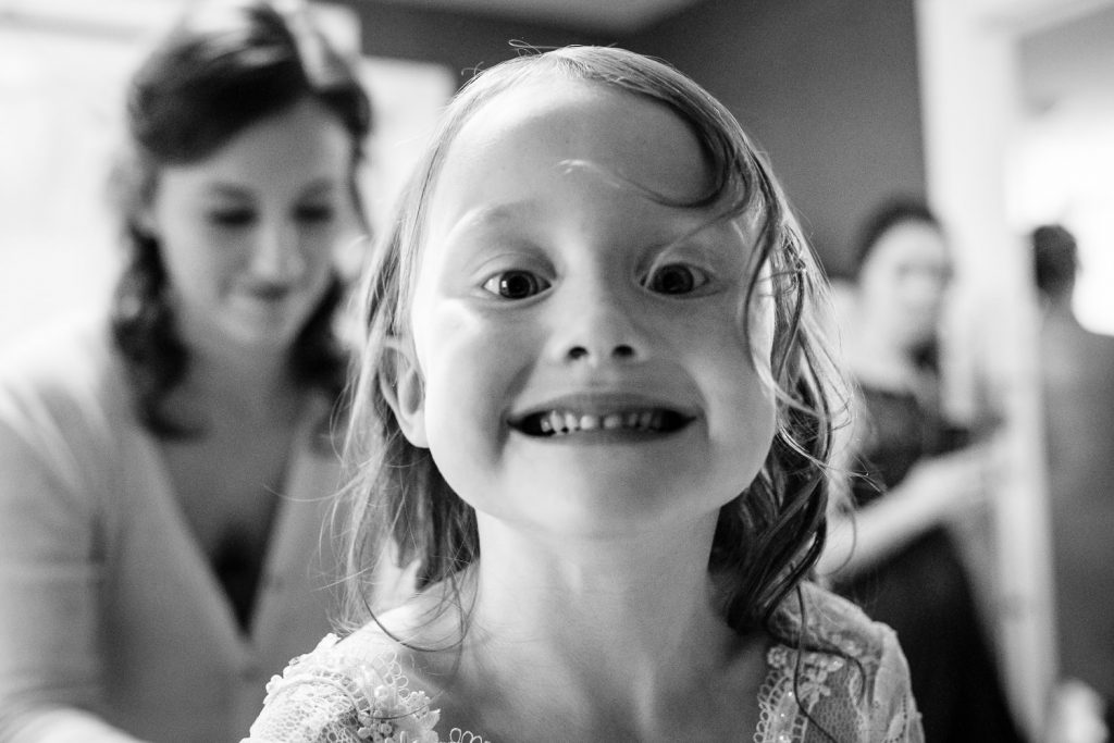 The daughter of the bride makes silly faces as she puts on her flower girl dress