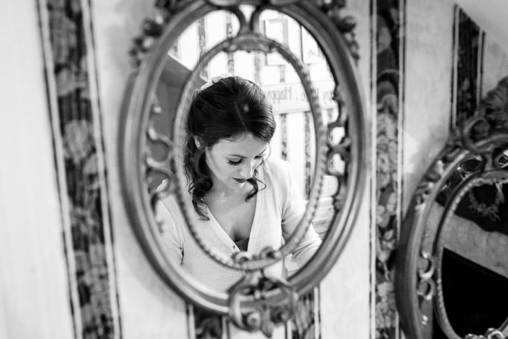 A bride gets ready in the reflection of an antique mirror