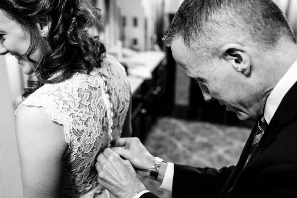 The father of the bride helps his daughter button up her wedding gown