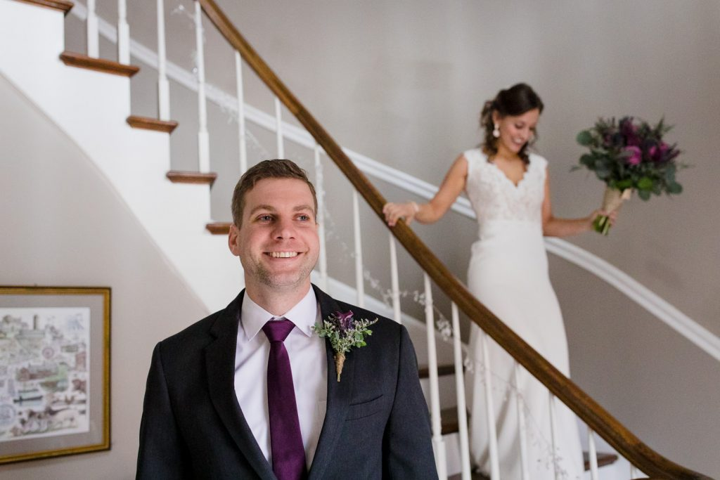 A bride walks down the stairs at the Five Bridge Inn to have a first look with her groom who is waiting downstairs