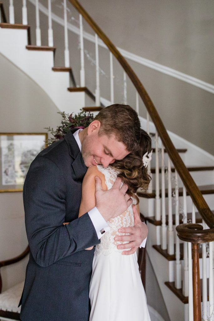 A groom embraces his bride after they share a first look