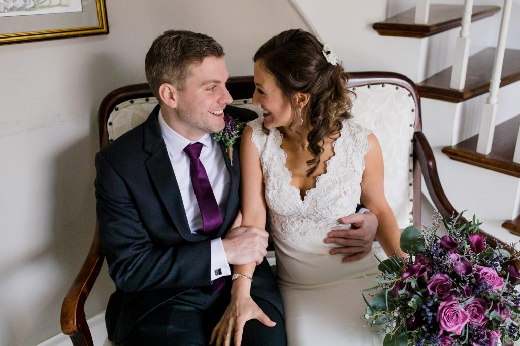 Wedding portrait of a bride and groom on a couch at five bridge inn