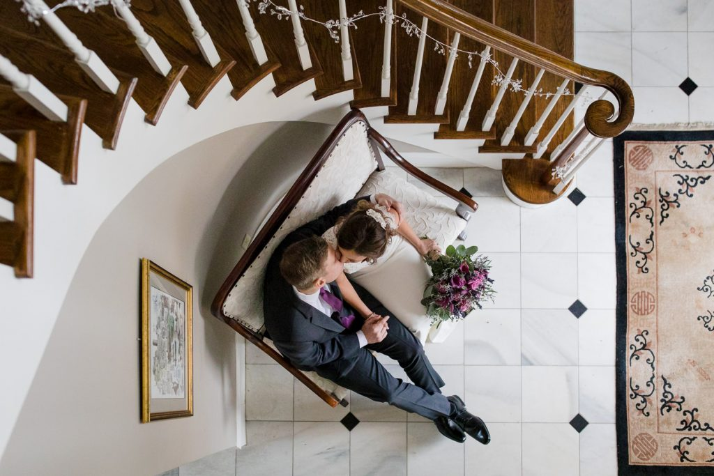 A view from above of a bride and groom in the lobby of the Five Bridge Inn at their wedding