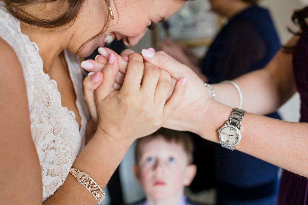 A little boy looks on as a bride warms up her hands