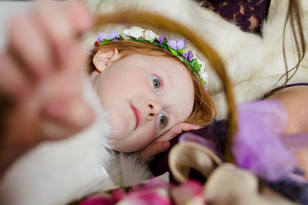 A bored flower girl lays down holding her flower basket