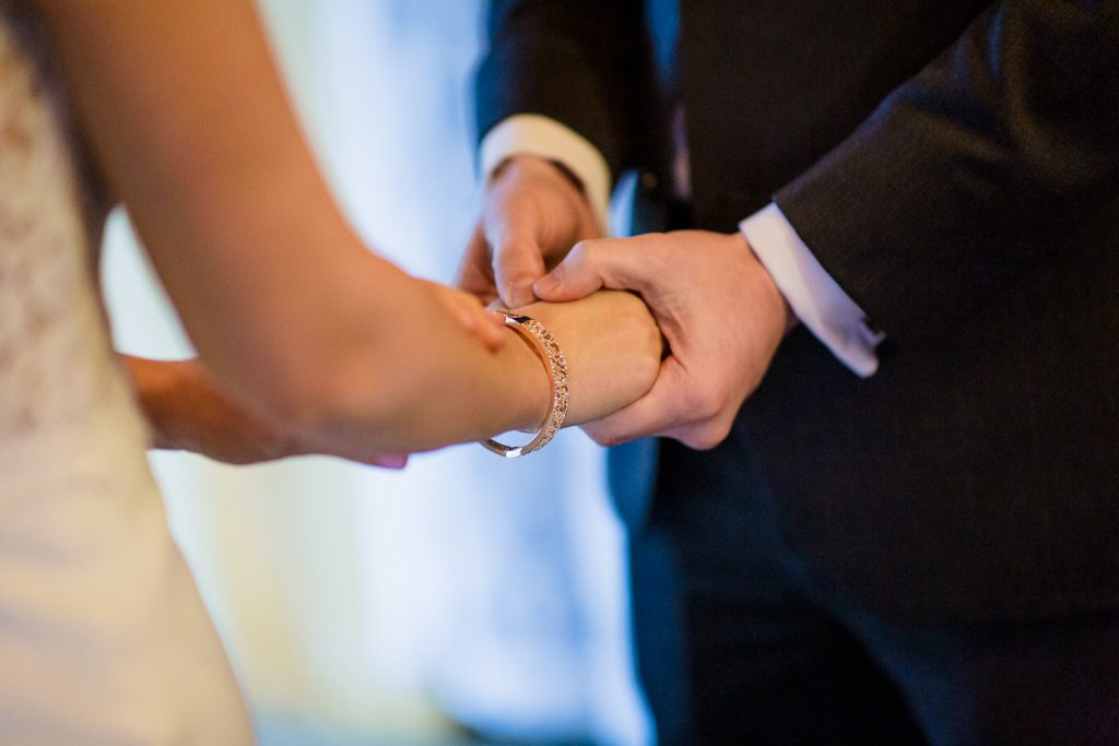 A bride and groom hold hands during their wedding ceremony