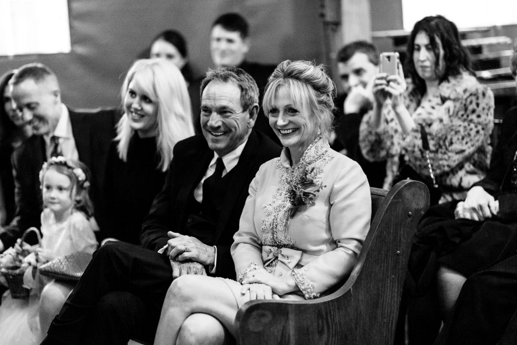 Parents smile as they watch their daughters wedding ceremony