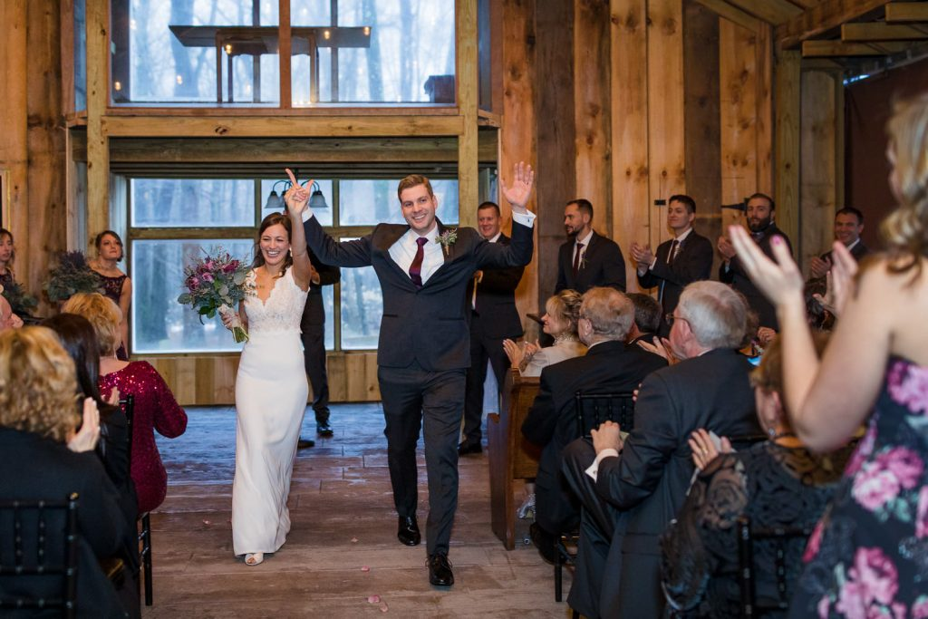 The bride and groom exit their wedding ceremony with arms high
