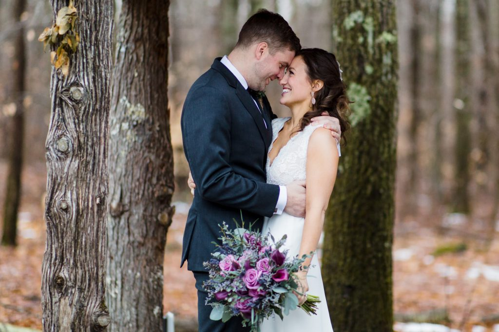 A bride and groom share a moment together amidst the trees in rehoboth ma