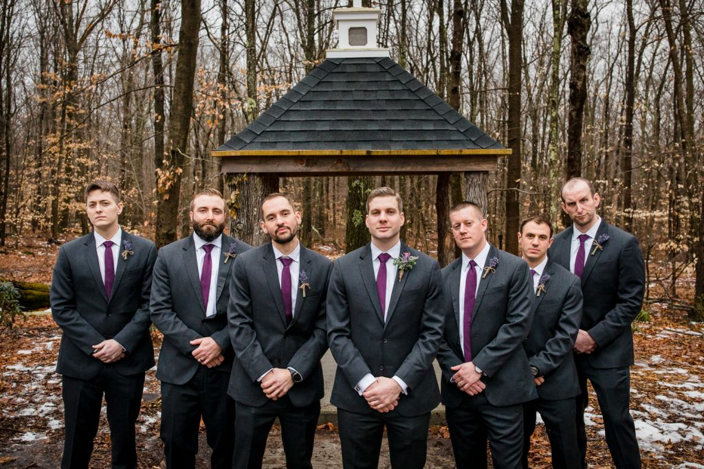 A groom and his groomsmen pose in front of the gazebo at five bridge inn