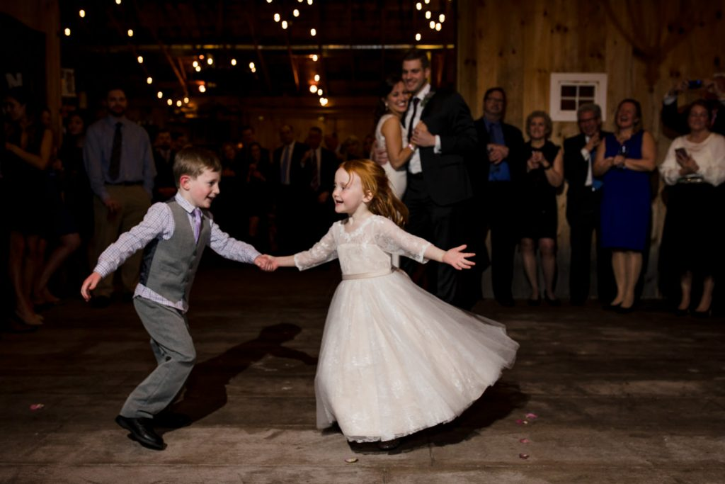 The flower girl and ring bearer steal the show during the first dance at this five bridge inn barn wedding