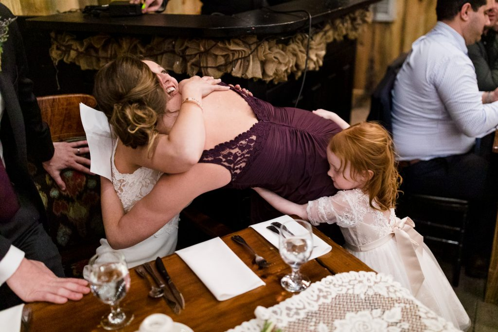 The bride and her daughter hug the maid of honor after her wedding speech